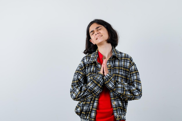 Маленькая девочка желает в рубашке, куртке и выглядит обнадеживающей. передний план. место для текста