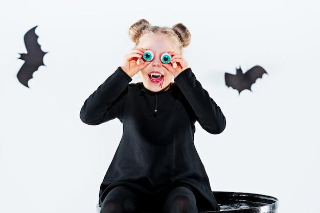 Strega bambina in abito lungo nero e accessori magici.
