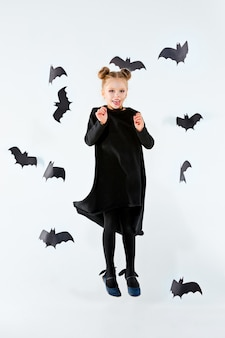 Little girl witch in black long dress and magical accessories.