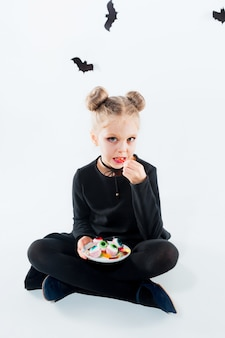 Little girl witch in black long dress and magical accessories