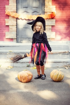 Little girl in witch costume celebrate halloween outdoor and have fun.