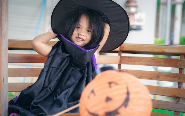 Little girl in a witch costume and lamp in halloween