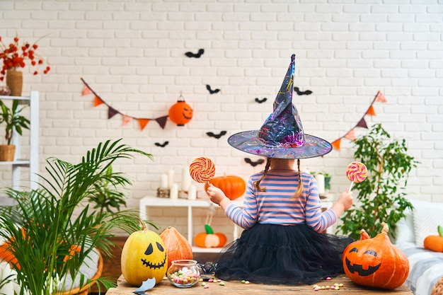 Little girl in a witch costume sitting at a table