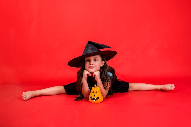 A little girl in a witch costume and with a hat is sitting on a string with a pumpkin on a red background with a copy of the space