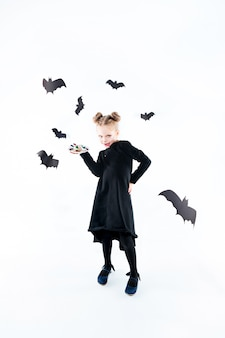 검은 긴 드레스와 마법의 액세서리에 어린 소녀 마녀. 할로윈