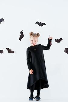 Маленькая девочка-ведьма в черном длинном платье и волшебных аксессуарах.
