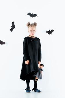 Маленькая девочка-ведьма в черном длинном платье и волшебных аксессуарах