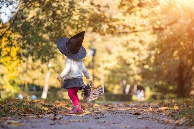 Little girl witch walks in the autumn forest with a basket of leaves.