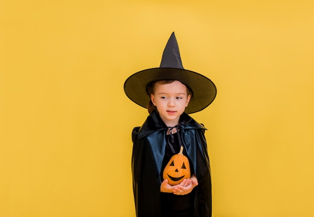 Little girl witch with an orange pumpkin with a face stands and looks away on a yellow isolated