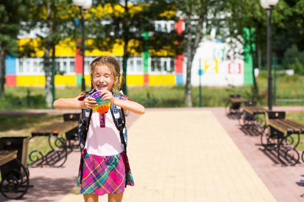 Маленькая девочка с рюкзаком и в школьной форме в школьном дворе играет в игрушку-поп.