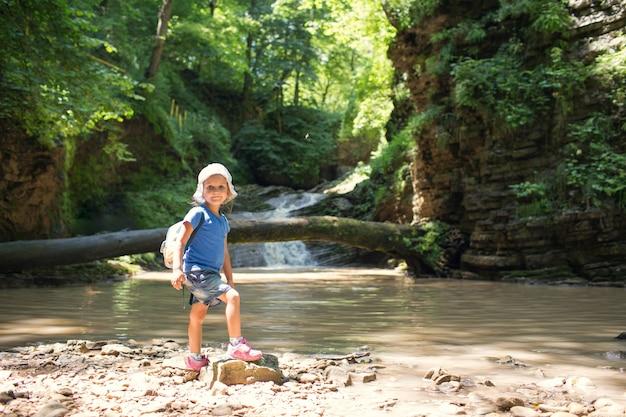 滝の山でのトレッキングでバックパックを持つ少女