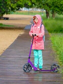 Маленькая девочка с рюкзаком на спине едет на скутере в городском парке