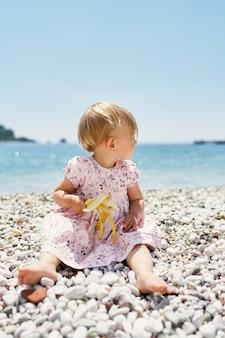 그녀의 손에 바나나를 들고 있는 어린 소녀는 그녀의 머리를 옆으로 돌리는 자갈 해변에 앉아 있다