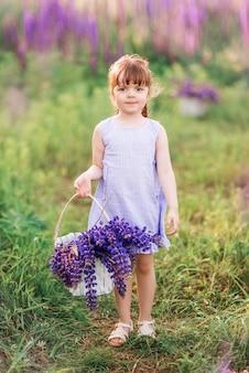 紫色の花のバスケットを持つ少女。自然の中の子供