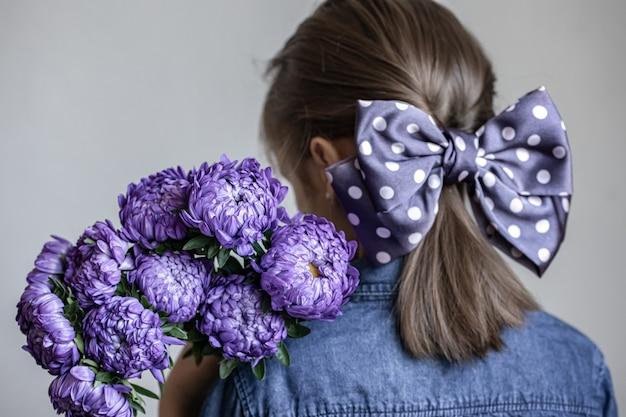 Маленькая девочка с красивым бантом на волосах держит букет синих хризантем, вид сзади.