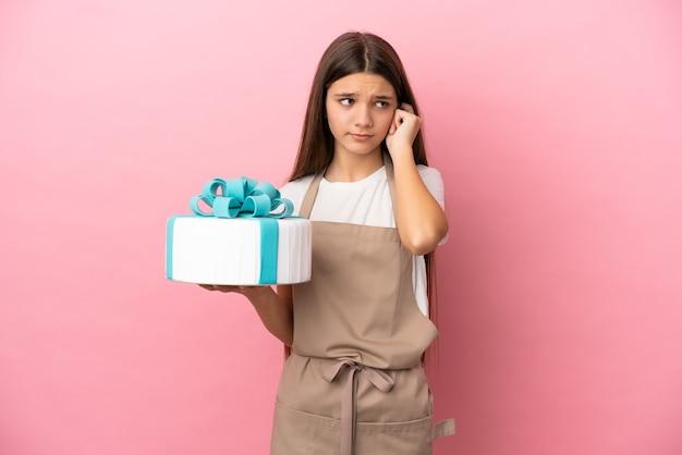 孤立したピンクの背景の上に大きなケーキを持つ少女はイライラして耳を覆っています