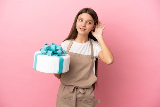 耳に手を置くことによって何かを聞いている孤立したピンクの背景の上に大きなケーキを持つ少女