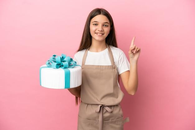 Маленькая девочка с большим тортом на изолированном розовом фоне показывает и поднимает палец в знак лучших