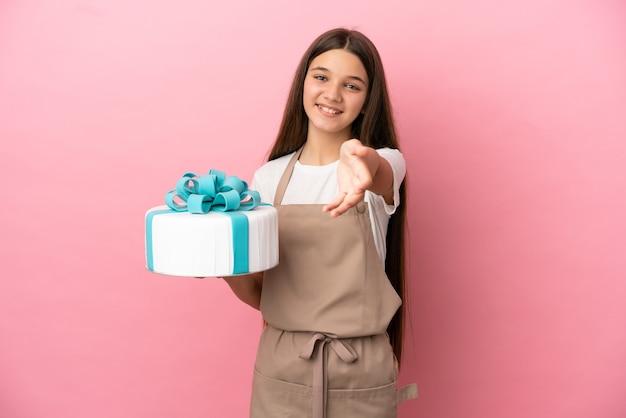 좋은 거래를 닫기 위해 악수하는 격리 된 분홍색 벽 위에 큰 케이크와 어린 소녀