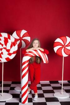 孤立した赤い壁に大きなクリスマスキャンデー杖を持つ少女。巨大なクリスマスキャンディー。お菓子