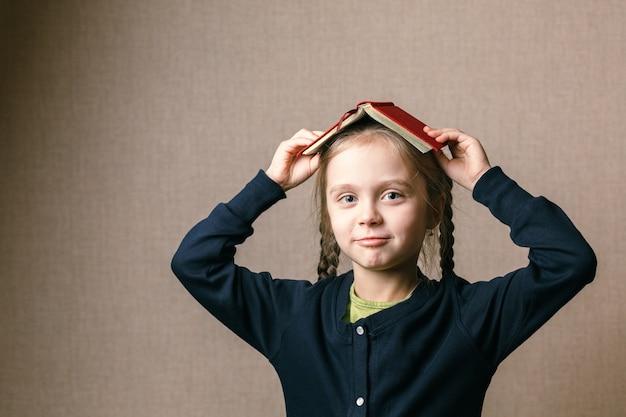 彼女の頭の上に本を持つ少女