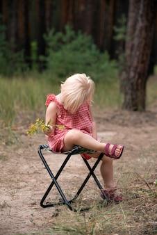 野花の花束を持った少女は恥ずかしそうに頭を下げた。子供は森の中で折りたたみ椅子で休んでいます。垂直フレーム。