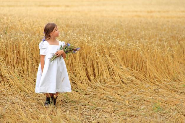 Маленькая девочка с букетом полевых цветов в руках в пшеничном поле.