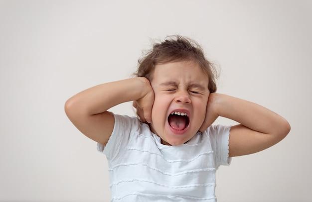 Маленькая девочка с ярким фоном кричит, закрыв глаза и уши.