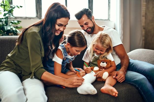 Маленькая девочка со сломанной ногой на диване. мама, папа и две дочери рисуют фломастерами на гипсе. вся семья веселится дома.