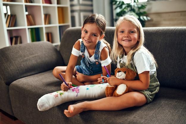 Маленькая девочка со сломанной ногой на диване. две сестры рисуют фломастерами на гипсовой повязке. дети веселятся и играют на диване в гостиной.