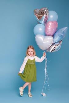 파란색 표면에 풍선의 무리와 함께 어린 소녀
