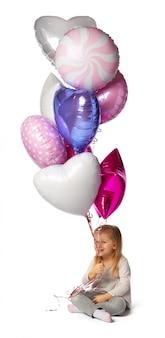 Маленькая девочка с кучей воздушных шаров сидит на белом фоне