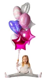 Маленькая девочка с букетом воздушных шаров на белом фоне