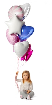 Маленькая девочка с букетом воздушных шаров