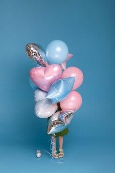 파란색 표면에 그녀의 얼굴을 덮는 풍선의 무리와 함께 어린 소녀