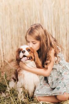 자연에서 여름에 노는 카발리에 킹 찰스 스패니얼 강아지와 어린 소녀