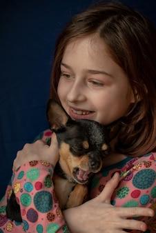 チワワを持つ少女。チワワを持っている女の子。彼女の腕に彼女のペットを持つ少女。ブラックブラウンホワイトカラーのチワワ。子供たちは動物が大好きです。女の子とチワワ。子供たちは動物が大好きです