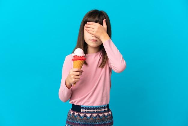 Маленькая девочка с мороженым корнет, изолированные на синем фоне, закрывая глаза руками. не хочу что-то видеть