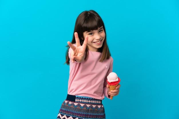 파란색 배경에 행복하고 손가락으로 세 세에 고립 된 코넷 아이스크림 어린 소녀