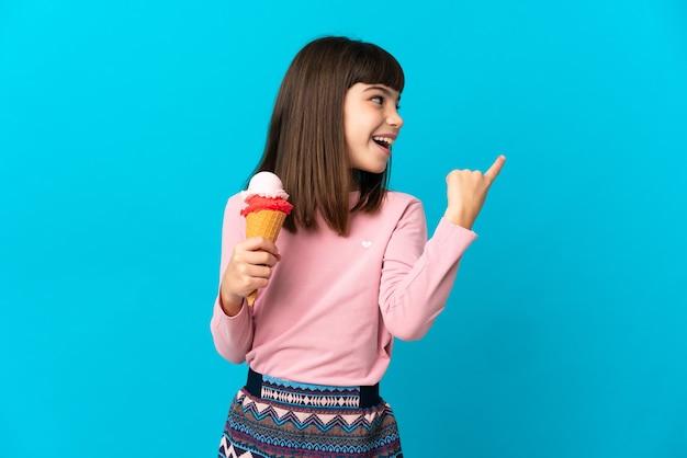 Маленькая девочка с мороженым корнетом изолирована на синем фоне, намереваясь реализовать решение, подняв палец вверх