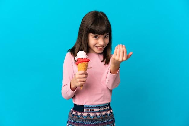 손으로와 서 초대하는 파란색 배경에 고립 코 넷 아이스크림 어린 소녀. 와줘서 행복해