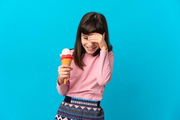 笑い青の背景に分離されたコルネット アイスクリームを持つ少女