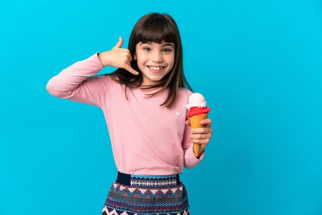 電話のジェスチャーを作る青い背景で隔離のコルネットアイスクリームを持つ少女。コールバックサイン