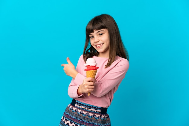 Маленькая девочка с мороженым корнет, изолированные на синем фоне, указывая назад