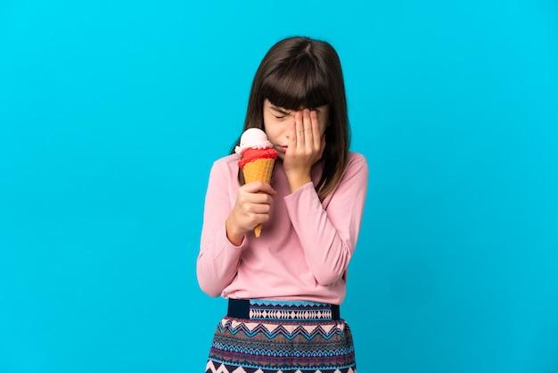 疲れて病気の表情で青い背景に分離されたコルネットアイスクリームを持つ少女