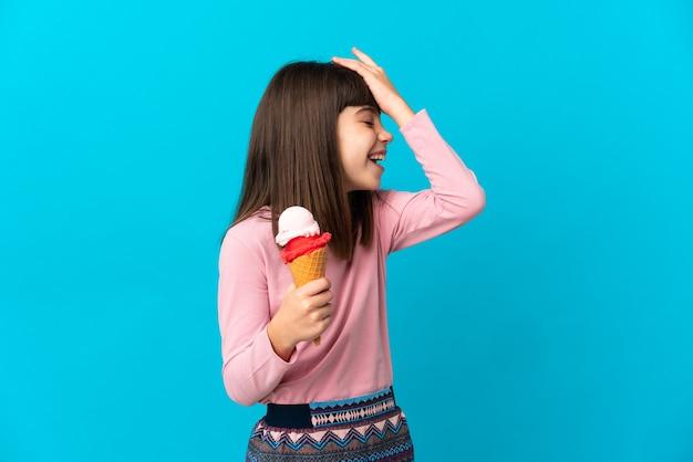 파란색 벽에 고립 된 코넷 아이스크림을 가진 어린 소녀는 뭔가를 깨달았고 해결책을 의도했습니다.