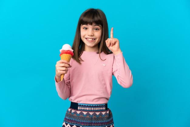 素晴らしいアイデアを指している青い壁に分離されたコルネットアイスクリームを持つ少女