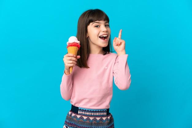코넷 아이스크림을 가진 어린 소녀는 손가락을 가리키는 아이디어를 생각하는 파란색 벽에 고립