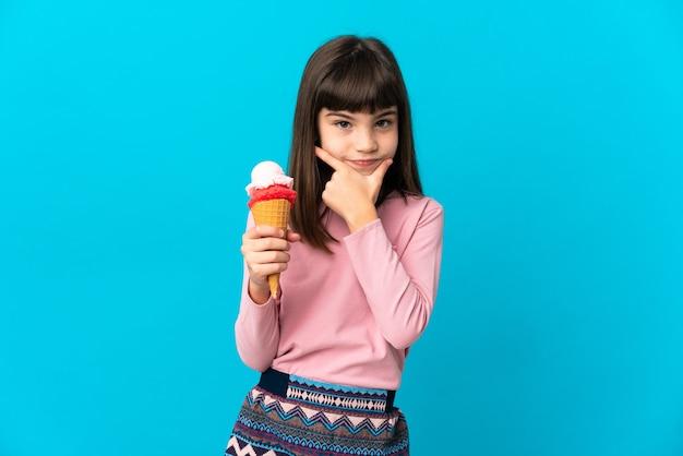 파란색 벽 생각에 고립 된 코 넷 아이스크림 어린 소녀