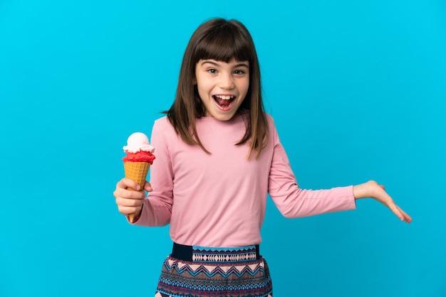 충격 된 표정으로 파란색 벽에 고립 된 코넷 아이스크림 어린 소녀